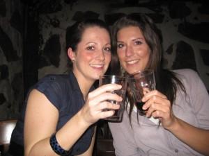 Jessy und Fenja sitzen am Tisch und stoßen mit 2 Gläsern an